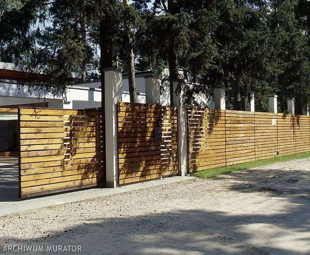 Przykład bardzo udanego połączenia drewna z nowoczesną bryłą budynku. Wyrafinowane w swej prostocie ogrodzenie podkreśla urodę domu i – powtarzając pewne elementy elewacji – tworzy z nim nierozerwalną całość