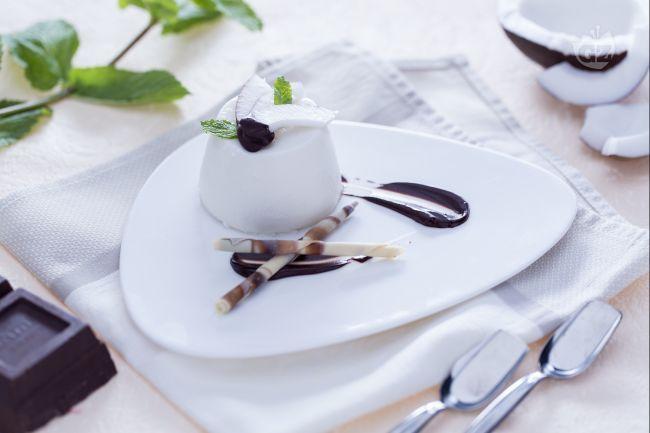 La panna cotta al cocco con salsa di cioccolato è un delicato e fresco dessert al cucchiaio preparato con latte di cocco e una salsa di cioccolato.