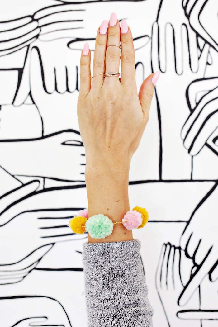 female arm with pale pink nail polish, and gray sleeve, wearing handmade pompom necklace, gift ideas for mom, in light green, pink and yellow