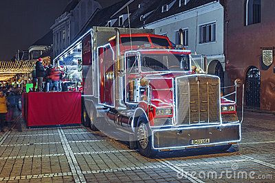 Brasov, Romania - December 12, 2015: Nightfall scene with Red Coca-Cola truck, decorated with Christmas lights, in the Council Square.