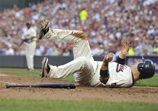 Minnesota Twins' Josh Willingham flips after failing to score from third on a bases-loaded fielders choice in the sixth inning of a baseball game against the Oakland Athletics Saturday, July 14, 2012 in Minneapolis
