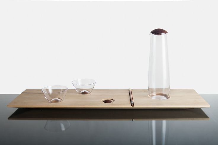 """The tray with glass set """"Truffle"""" is inspired by Japanese aesthetic and also by opened bonbonniere where are some of chocolates already missing. So one is able to move with chocolates as he wishes. The same idea is attached to the tray. It contains a glass set for two people. But there are three spots on wich you can place cups. So you can move wooden truffles and glass cups in order to achieve your own combination."""