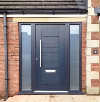 Modern front door and entrance. Door in black. Opaque glass sidelight panels on each side of the door.