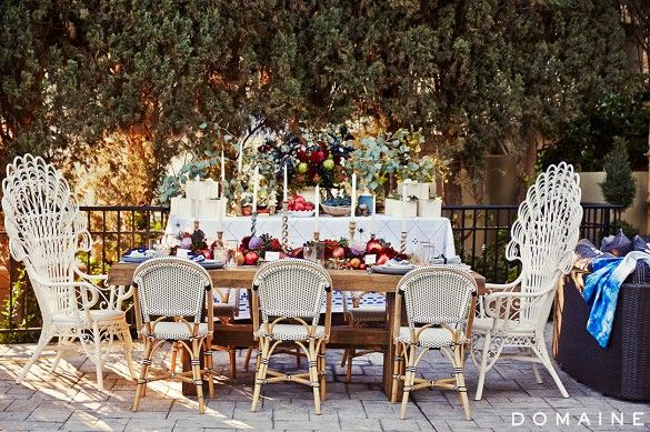 Fall season backyard dinner party at rustic wooden table with Serena & Lily woven and peacock chairs.