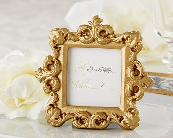 """Royale"" Gold Baroque Place Card/Photo Holder. When uncompromising elegance is expected, let your moment live up to those expectations. Our stunning, gold baroque frame adds instant grandeur to any setting--and can also add an unexpected, eclectic kick to an ultra-hip celebration. Features and facts:  Beautifully detailed, resin, baroque frame with a matte-gold finish Frame measures 4"" h x 3 1/2"" w Place card holder included"