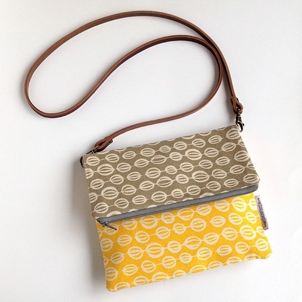 fold over cross body bag screen printed in grey and yellow in seedpods design with leather strap