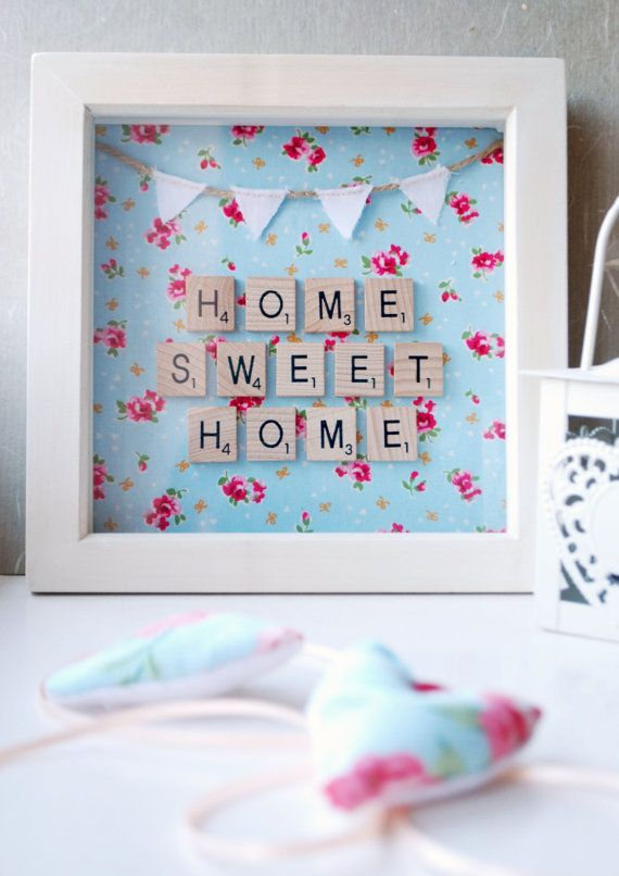A cute piece of scrabble wall art which is perfect as a gift for new home owners, or for those simply wanting to add a little country charm to their kitchen, dining, living or bedroom.  Scrabble tiles are carefully set upon a Cath Kidston style fabric, and encased in a small white painted frame measuring 19cm x 19cm. A delicate white bunting at the top finishes the piece off, which has been lovingly sewn onto a length of twine.  If you would prefer a different background or different…