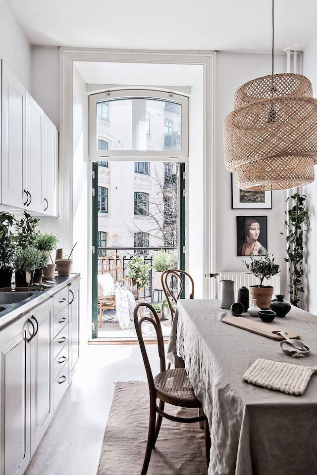 Just something about this kitchen. Love the doors going out to the balcony and the linen tablecloth and bistro chairs. Lots of greenery too and a rug in a dining area makes it cosy. #scandi #scandinavian #kitchen