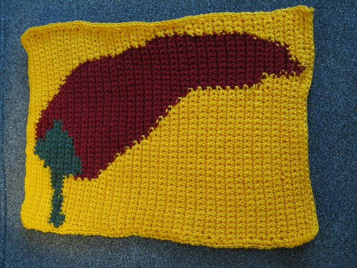 """Chili pepper hot pad.  My sister-in-law has chili pepper curtains in the kitchen, so I made her matching hot pad and pot holders.  The photo was take before it was blocked.  The hot pad is about 14"""" across.  I used mercernized cotton because that was the only yellow I found that matched.: Photo"""