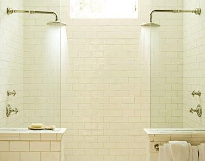 walk in shower with his and her shower heads, and subway tile.