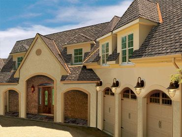 Light Yellow Stucco With Grey Shingles Roofing Services