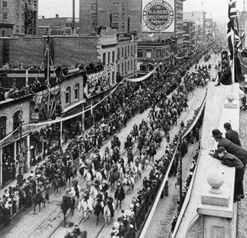 Cowboys ride down 8th Ave and 1 St SW by the Alberta Hotel (left of centre) in September of 1912 as they participate in the Calgary Exhibition and Stampede parade, Calgary, Alberta. View possibly taken from top of Clarence or Norman Blocks.