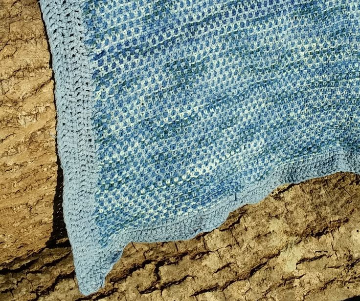 A kitchen towel made in linen stitch. 3 different colours cotton yarn: one multicolour blue, one medium blue in a slightly thicker quality, and on unravelled repurposed blue (also used for the edging).