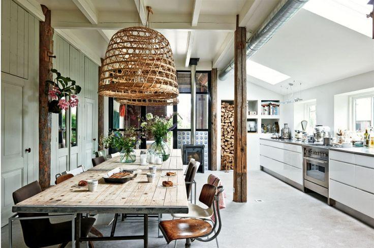 De oude binten in de keuken zijn origineel. De ManoXL keuken is van Kvik, het Solitaire-fornuis van Bosch. Op de vloer ligt gevlinderd beton. De hanenmanden kocht Maamke bij Loods 5. 'Wij zochten grote lampen, maar ze moesten wel transparant zijn. Als je in de woonkamer staat, wil je wel naar buiten kunnen kijken.' De vlinderstoelen zijn van Arne Jacobsen, de houten bureaustoelen vonden ze bij Combitex, de fauteuil is van Arco. Rob maakte de tafel zelf. Het houten blad rust op een onderstel…