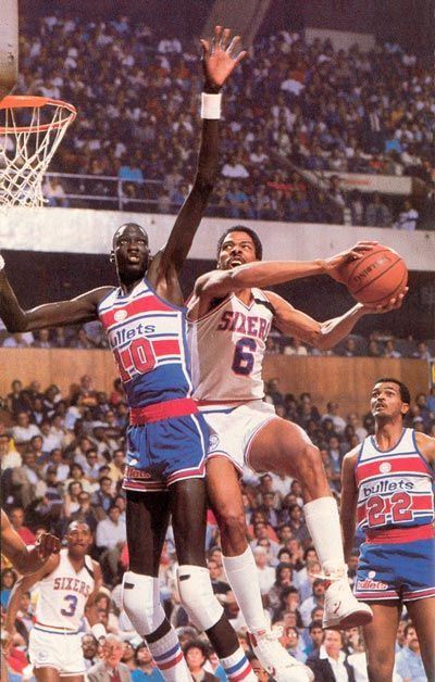 "Manute Bol (1962 - 2010) NBA basketball player from Sudan, known for his great height (7' 7"") and shot-blocking ability during his 10 year career.  Bol (left) defending a shot by Julius Irving of the 76ers."