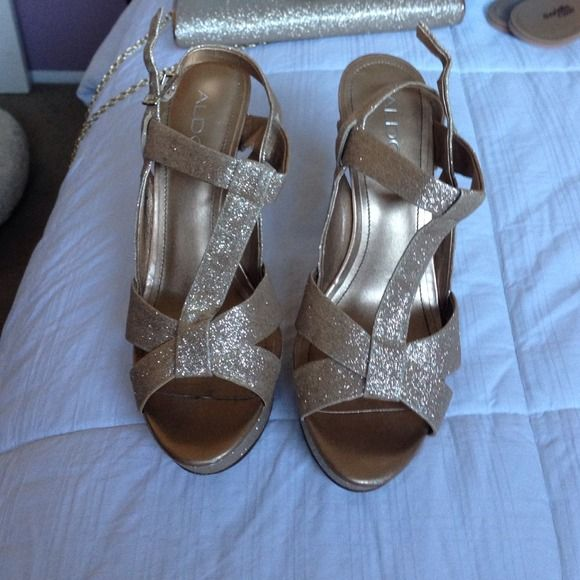 Shiny gold sandal heels Shiny gold platform t strap sandle pumps.  Worn once for wedding.  Minor wear heel has a little bit of dirt shown in pic.  Matching clutch in other picture ALDO Shoes Heels