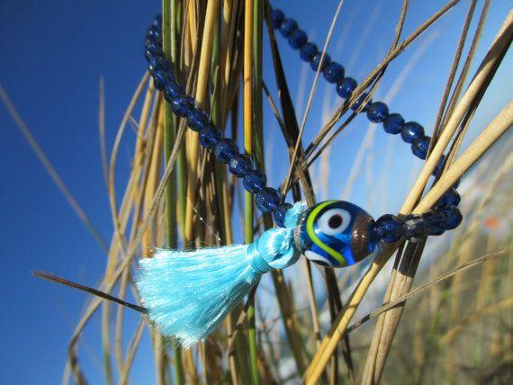 Ce pompon aqua fait main stretch bracelet en perles à facettes de cristal tchèque dispose et une perle oeil travaillé au chalumeau, dont les croyances traditionnelles dire protéger le porteur contre «le mauvais œil». Main-tendu et noué deux fois pour plus de solidité et de sécurité sur la prime cordon bleu clairement. Pompon soyeux couleur bleu aqua.  Bracelet sera livré dans une pochette en organza pour le stockage en toute sécurité ou les dons gracieux.  Design, photographie et…