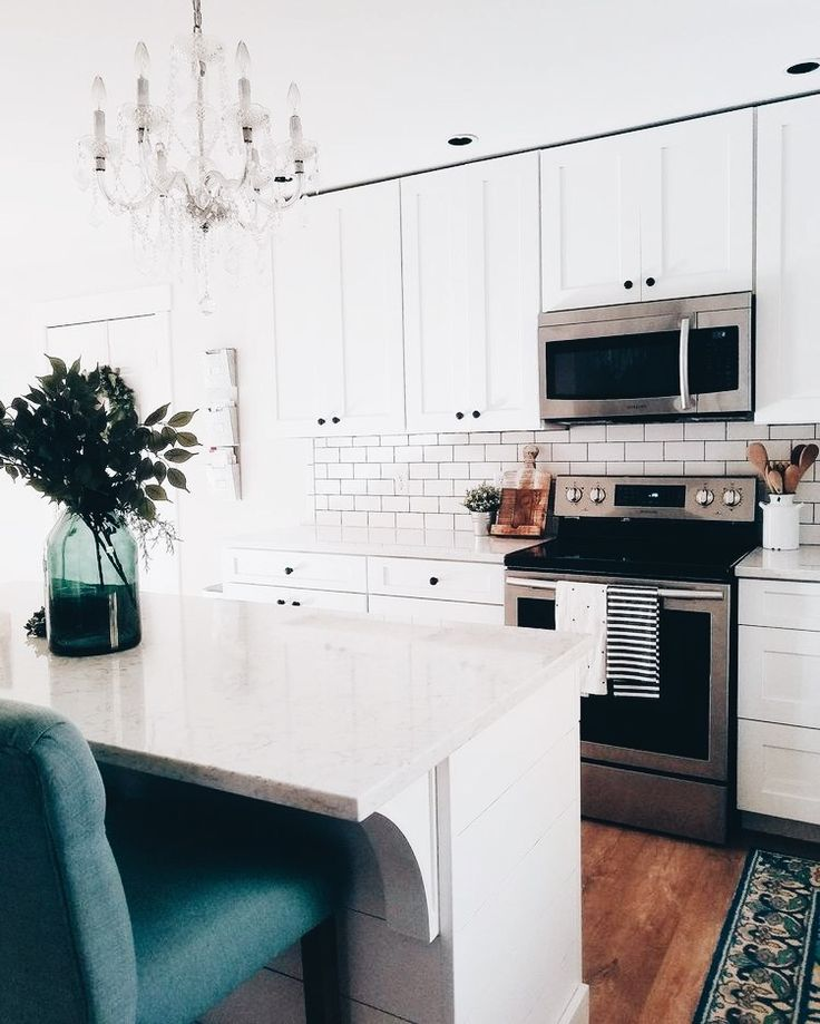 simple white with black details and wood accents with just a small pop of color ... might just change the chandelier for something more modern or industrial looking and maeke the barstools a basic neutral color or industrial with wood or a bluegray fabric so that the only pop of color is on the rug and the counter