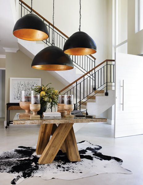 Open space entry - gorgeous black and copper pendants over a chunky rustic table... La Grange