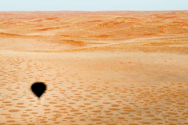 Le dune rosse nel Namib Rand Nature Reserve viste dalla mongolfiera alle luci dell'alba. I cerchi nella sabbia rossa sono i curiosi fairy circles, cerchi delle fate. Ancora oggi si dibatte sulle possibili origini:  termiti, altri insetti, le piante stesse che competono per l'acqua.  La spiegazione più affascinante resta comunque quella della leggenda: gli spiriti dei defunti, che ballano in cerchio, impediscono alla vegetazione di crescere all'interno del cerchio stesso.