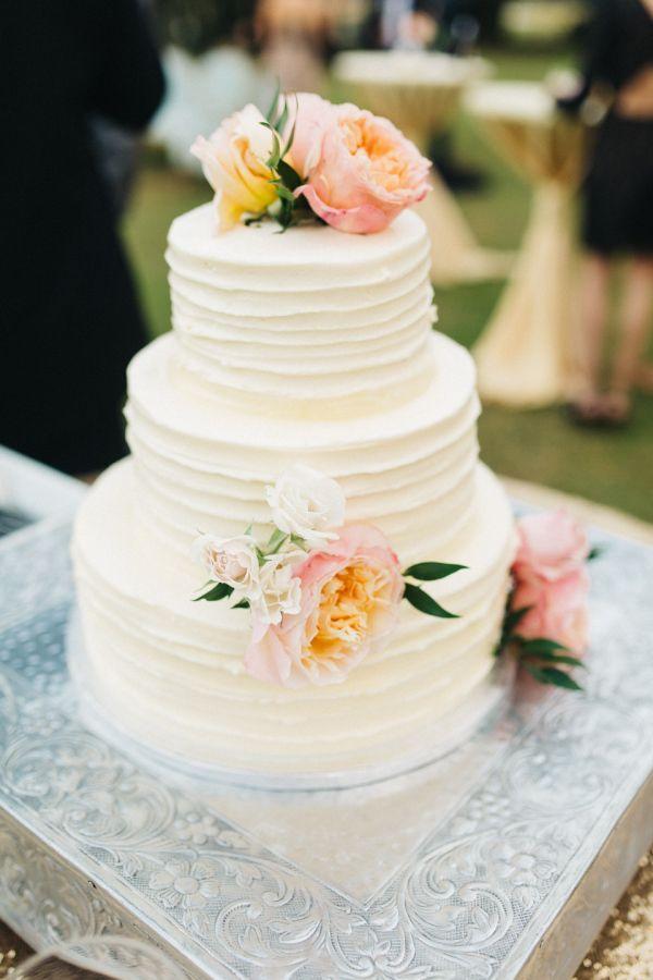 Pretty floral topped white wedding cake: http://www.stylemepretty.com/south-carolina-weddings/edisto/2016/01/11/elegant-timeless-waterside-southern-wedding/   Photography: Caroline Ro - http://carolinero.com/