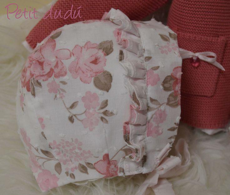 Conjunto de blusa, capota y cubrepañal confeccionada en un plumeti rosa clarito, combinado con uno liso, de escote redondo con un doble cuello fruncido. El cubrepañal lleva un gran lazo y la capota doble corona plisada.
