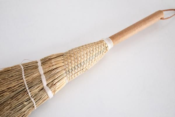These short handled straw brooms have been carefully crafted from sorghum stems woven into place with white threads : No.56, Penzance, Cornwall