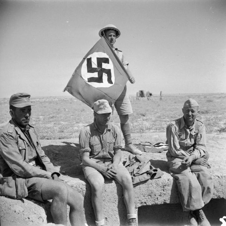 BRITISH ARMY NORTH AFRICA 1942 (E 12817)   A British soldier poses behind three German prisoners with a captured Nazi swastika flag, 2 June 1942.