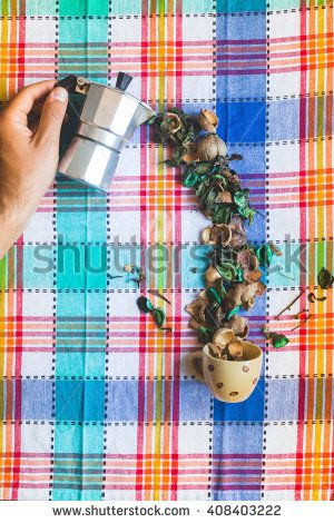 Hand pouring flowers from an Italian coffee maker into a cup