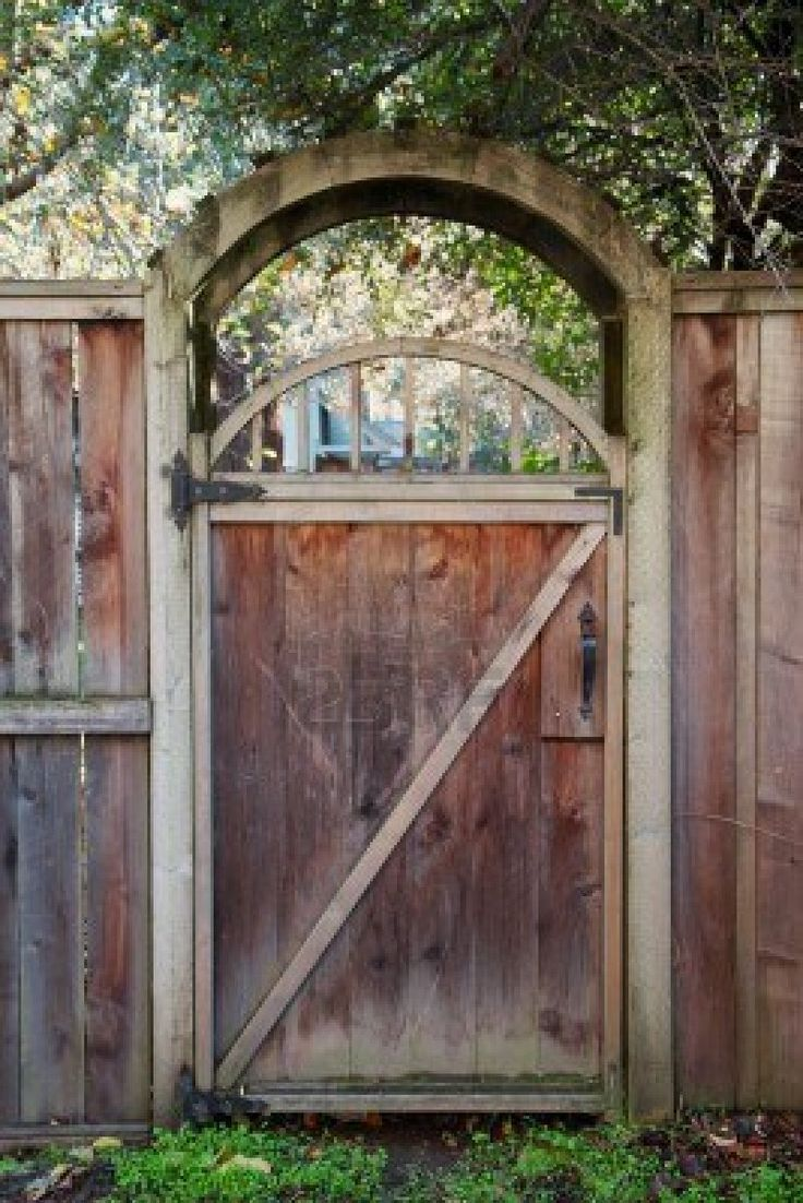 Arched entry of a worn redwood fence door stock photo