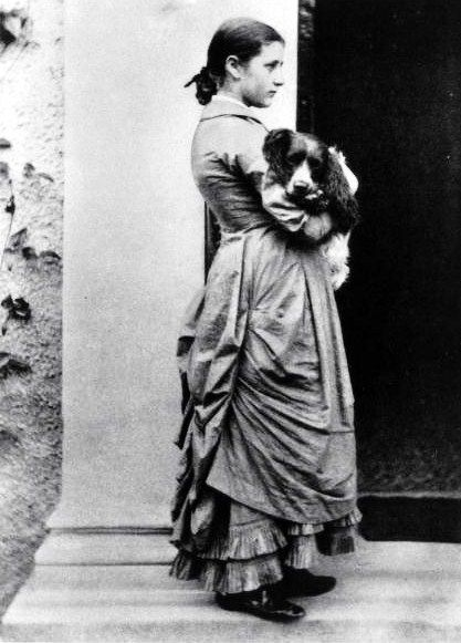 British author/illustrator Beatrix Potter posing outside with her dog at age 15. Photograph by Rupert Potter. UK, 1907.