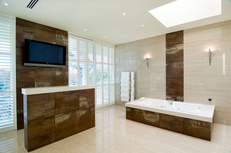 Every detail of the bathroom layout has been carefully considered, with the spa positioned for easy viewing of the television and the toilet area which encompasses a toilet and bidet, hidden out of sight behind a unique feature wall. Super luxury bathroom. Designed & built by http://bubblesbathrooms.com.au/