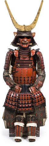 A red lacquer armor Edo period (17th century) Laced in blue and comprising a russet-lacquer twenty-plate suji kabuto decorated with a five-lame copper and gilt-copper tehen kanamono with four red lacquer shinodare framed in gilt-copper and mounted with a five-lame hineno style shikoro scalloped on the top edges and finished in red lacquer fukigaeshi decorated with Buddhist emblems within circles in gold lacquer, the bowl signed Saotome Iehisa saku