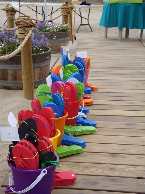 this welcome station gives away flip flops to wedding gueststhats our kind of reception