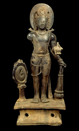 Brooklyn Museum: Vishnu: Hinduism's Blue-Skinned Savior  Vishnu. Eastern India (West Bengal) or Bangladesh, Gupta period, 5th century. Terracotta, 35 7/16 x 17 5/16 in. (90 x 44 cm). Private collection    This image of Vishnu shows him in his primary form, standing erect with three of his four attributes: the wheel or chakra, the conch shell, and the mace.  His fourth hand, now missing, probably held a lotus bud.