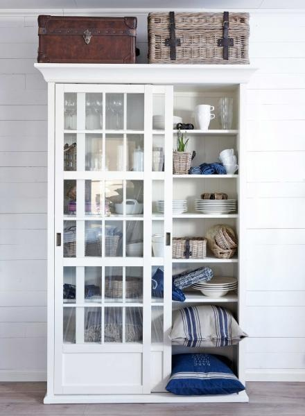 I love the height of this shelving unit with the divided glass sliding doors done in white. Lovely piece of furniture. I love the blue and white finds inside!