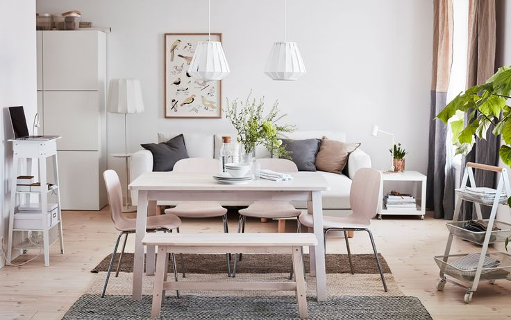 A medium-sized dining room furnished with a white stained solid birch table shown together with four birch chairs with chrome-plated legs and a white stained solid birch bench.