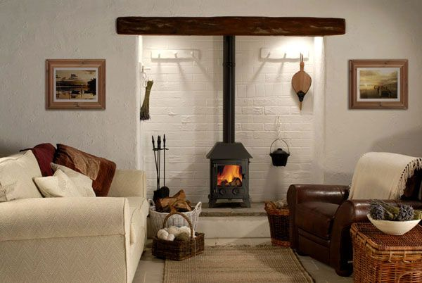 Cream and ivory working well with wicker and brown leather to make for a comfortable, stylish cottage Living Room. The painted brick wall behind the wood burner makes a great backdrop to showcase rustic accessories as well as a wonderful fire!