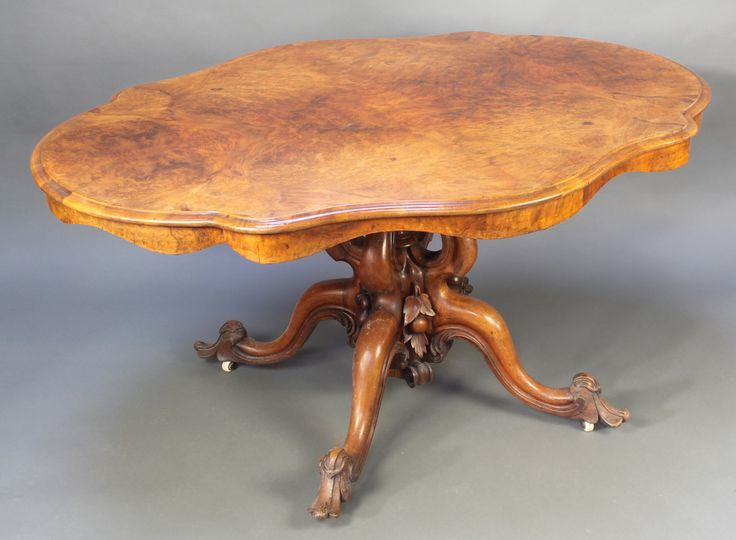 """Lot 884, A Victorian shaped figured walnut loo table raised on a heavily carved pillar and tripod base 28"""" x 57"""" x 45"""" est £180-220"""