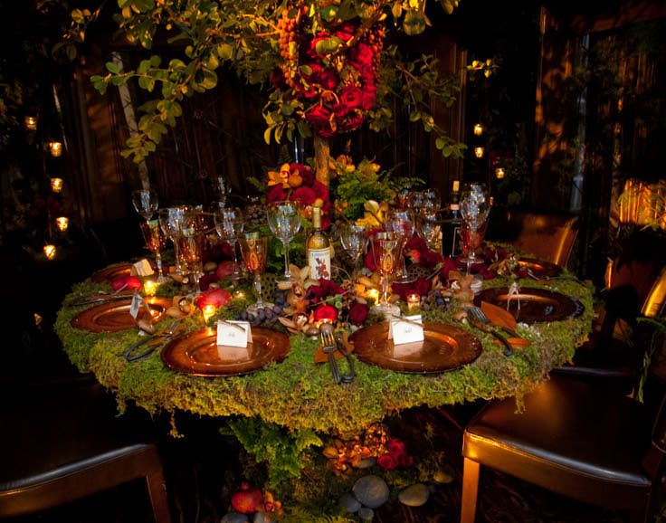Chinese Fringe Tree.  Moss covered table and planters.  Tiny, robust vignettes interlaced in the tree and on the table.  Copper tones for crackled chargers and goblets.  Red roses, purple artichokes, various wild flowers, winter pears, and pomegranates were used to bring in dark jewel tones as the accent color.