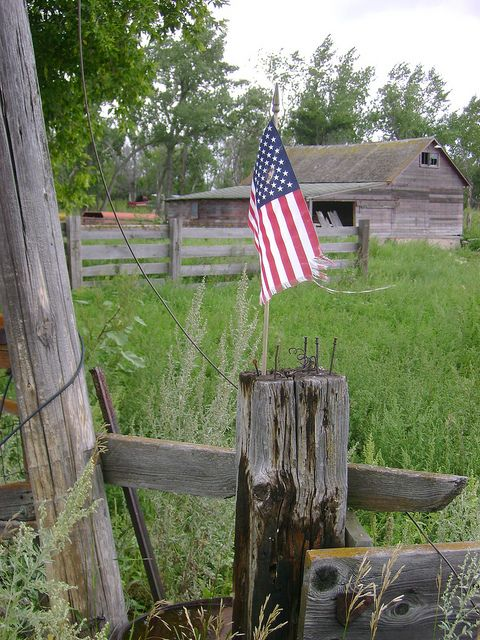 A tiny Old Glory in the middle of a rustic, rural setting.