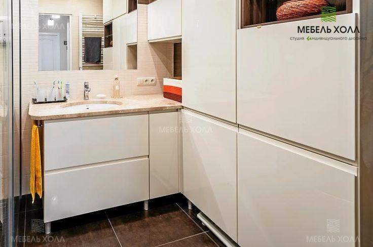 Комплект шкафчиков для ванной из МДФ покрытого пластиком молочного цвета. Столешница под умывальник выполнена из натурального камня