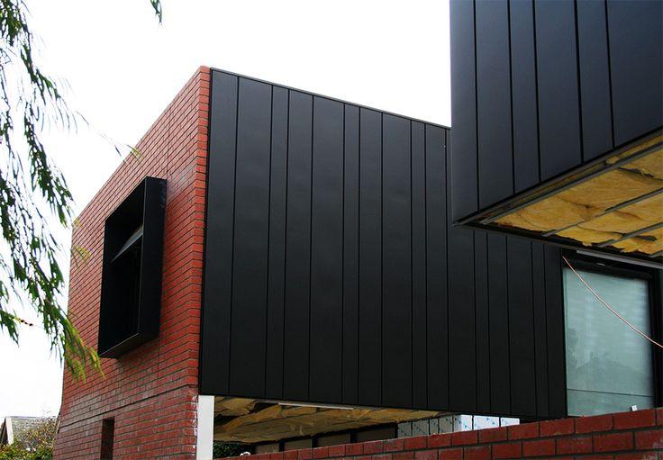 Casset Seam metal Panel next to brick
