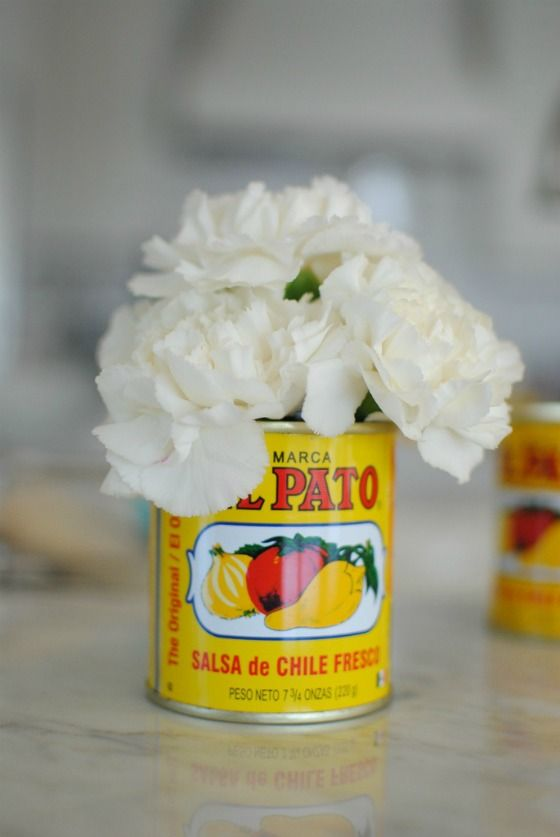 Easy Cinco De Mayo party ideas | Simple centerpiece of recycled salsa tin container with fresh carnations. This flower's natural spicy scent, long vase life, and wide range of colors is perfect for parties! Get them from your favorite florist for the best selection. You can also use Mexican Coke bottles for the vase.