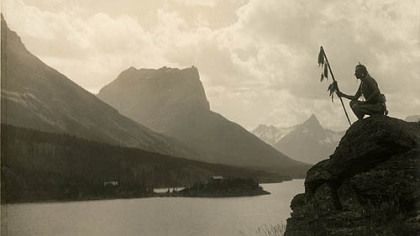 A Blackfoot Indian at St. Mary Lake at Glacier National Park. The Blackfeet were pressured to give up part of their reservation in Montana to create a national forest that eventually became Glacier National Park. Then the Great Northern Railway used many of them as tourist attractions in the company's advertising.