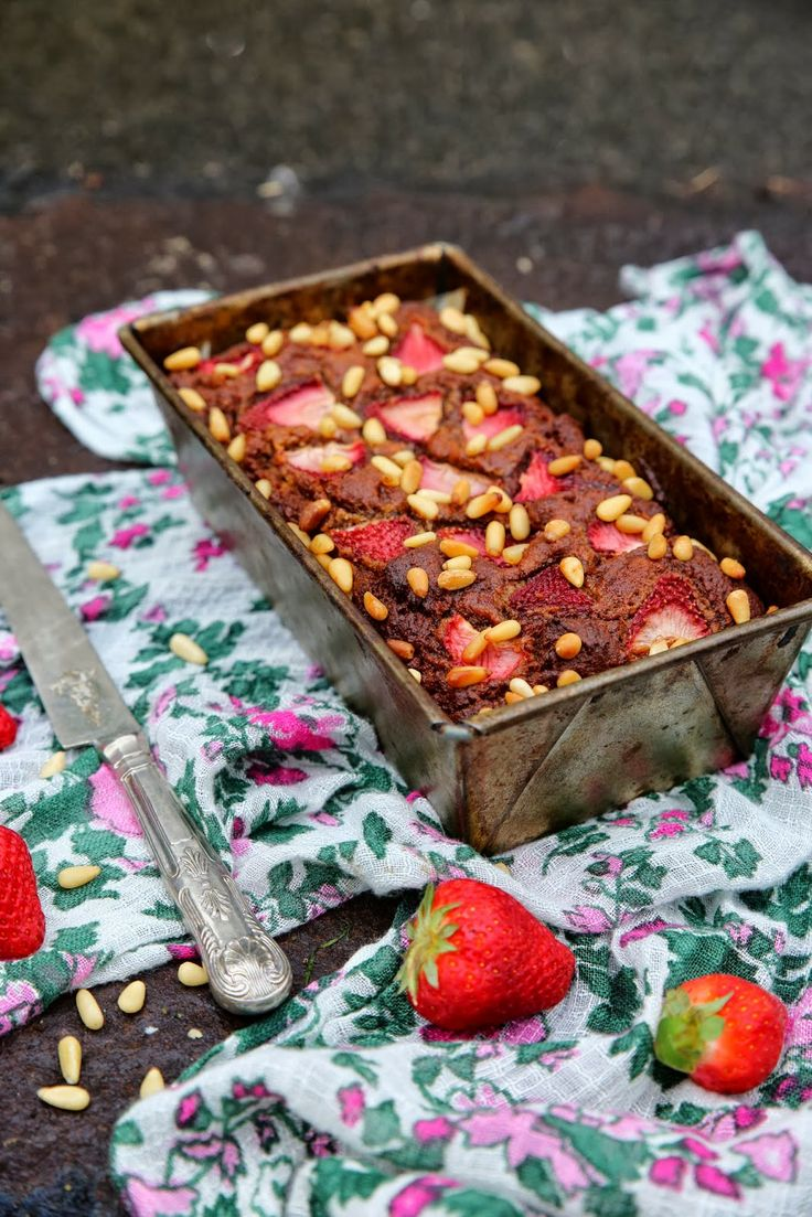 A MOIST DATE AND ALMOND CAKE TOPPED WITH STRAWBERRIES AND PINE NUTS