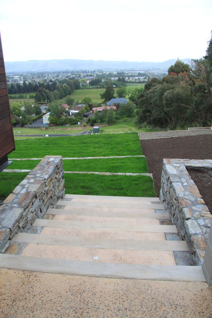 Unique stair design with schist walls leads down to terraced lawn on hillside of the property.