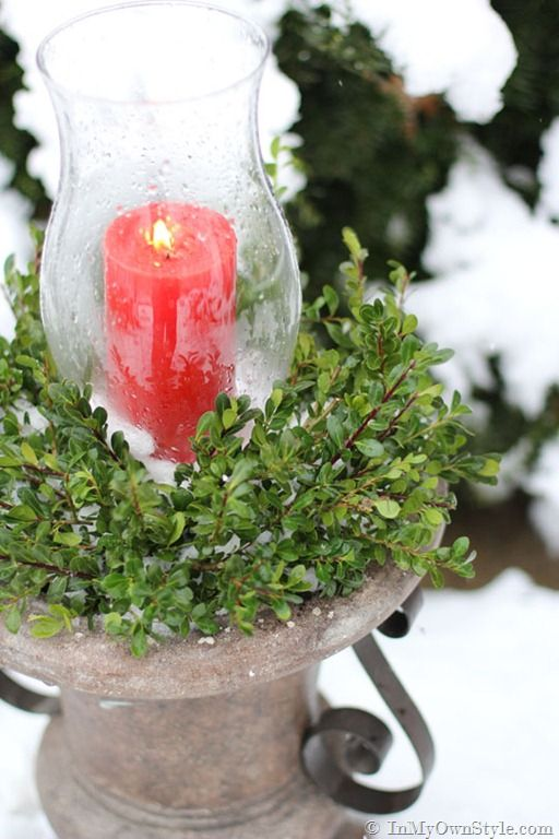 Outdoor urn hurricane with greenery and candle