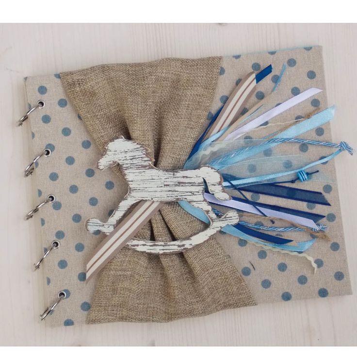 Χειροποίητο Βιβλίο Ευχών Βάπτισης αλογάκι καρουζέλ ξύλινο. Βιβλίο ευχών ντυμένο με μπεζ ύφασμα με μπλε παστέλ πουά, διακοσμημένο με ξύλινο χειροποίητο αλογάκι καρουζέλ.  Φύλλα :35 χρώμα φύλλων : γαλάζιο παστέλ  Υπάρχει η δυνατότητα να γράψουμε κάτω δεξιά σε κάθε σελίδα το όνομα του π