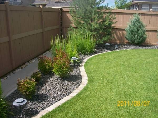Landscaping shrubs and decorative rock edging along fence in backyard.